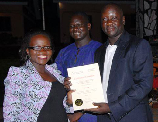 Ruth Atim receives a certificate of completion from Hoima Municipality Town Clerk Emmanuel Banya in Hoima during the launch of the association. Photo by Augustus Bigirwenkya